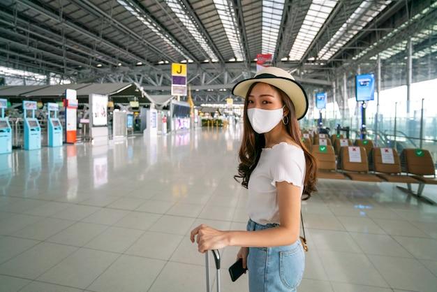 Aziatische vrouwelijke reiziger die gezichtsmasker draagt, houdt afstand met andere reizigers op de luchthaven