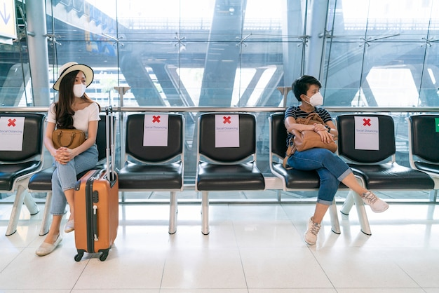Aziatische vrouwelijke reiziger die gezichtsmasker draagt, houdt afstand met andere reizigers