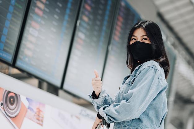Aziatische vrouwelijke reiziger die masker draagt, beschermt tegen coronavirus en toont duim met vertrouwen voor het vluchtinformatiebord