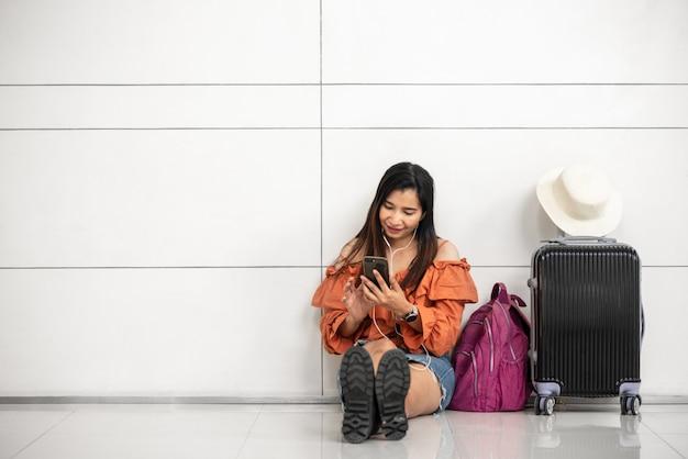 Aziatische vrouwelijke reiziger die op vlucht wachten en slimme telefoon buiten zitkamer in luchthaven met behulp van