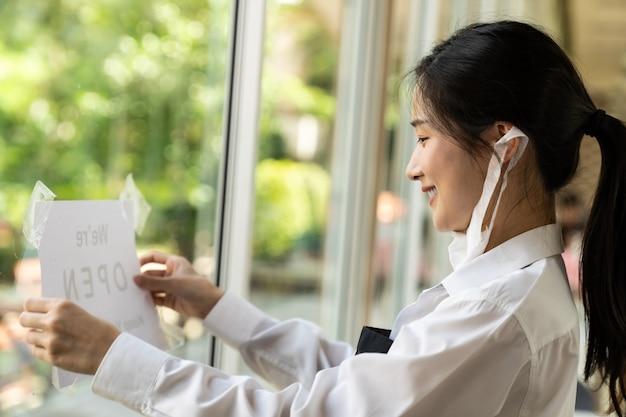 Aziatische vrouwelijke serveerster die open bewegwijzering met sociale afstand voor nieuw normaal restaurant zet. nieuw normaal restaurantlevensstijlconcept.