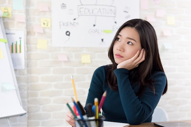 Aziatische vrouwelijke student die met hand op wang denkt
