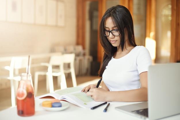 Aziatische vrouwelijke student huiswerk op de campus. oosters linkshandig meisje dat in een café, toekomstige advocaat of ingenieur werkt.