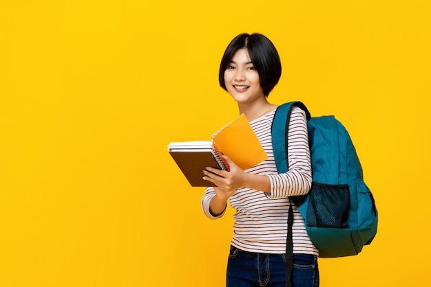 Aziatische vrouwelijke student met boeken van de rugzakholding