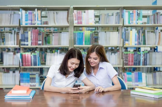 Aziatische vrouwelijke studenten die bij lijst zitten en tekstbericht lezen