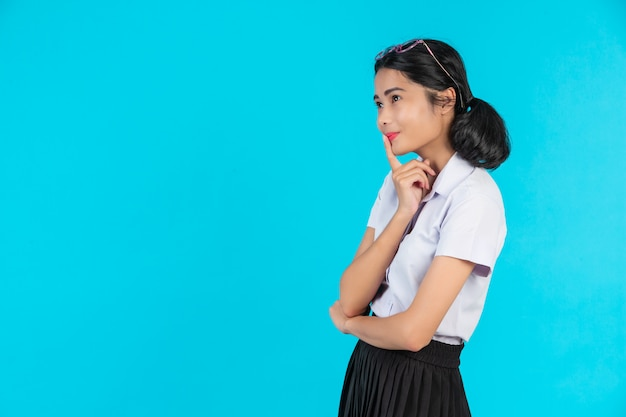 Aziatische vrouwelijke studenten die in verschillende posities op een blauw stellen.