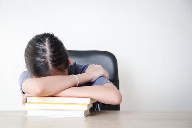 Aziatische vrouwelijke studenten studeren online vanuit huis. zit in de stress van het studeren. concept van sociale afstand, gebruik van technologie voor onderwijs. kopieer ruimte