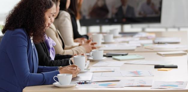 Aziatische vrouwelijke succesvolle zakenvrouw officier personeel van middelbare leeftijd in formele zakelijke kleding zitten in video teleconferentie vergaderruimte kijken grafiek grafiek diagram papierwerk documenten op tafel.