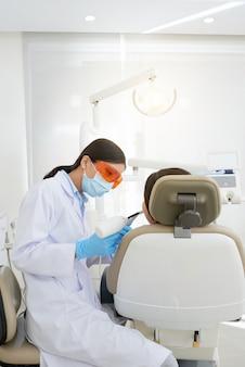 Aziatische vrouwelijke tandarts die de tand van de patiënt genezen die met ultraviolet licht vullen