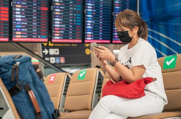 Aziatische vrouwelijke toerist die masker met behulp van mobiele telefoon, luchtvaartmaatschappij vluchtstatus zoekt