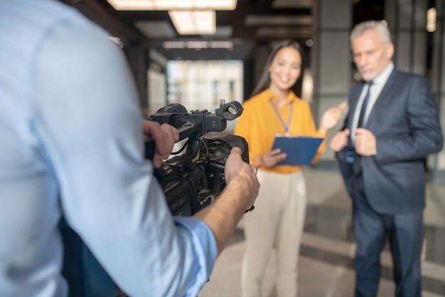 Aziatische vrouwelijke verslaggever die beige broek draagt die keurig glimlacht
