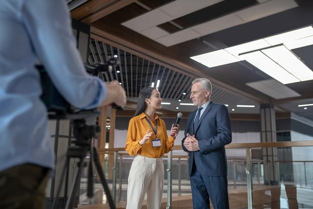 Aziatische vrouwelijke verslaggever in beige broek die vragen stelt aan grijsharige man