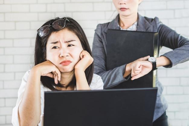 Aziatische vrouwelijke werknemer saai met baas