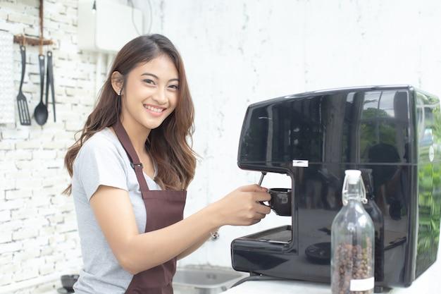Aziatische vrouwen barista die en aan camera in koffiewinkelteller glimlachen kijken