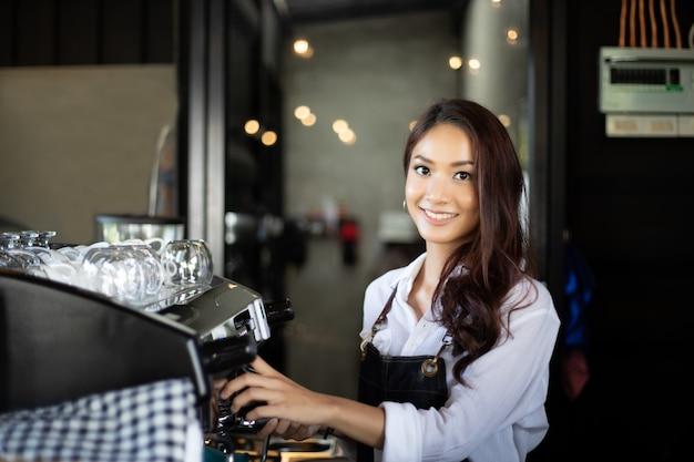 Aziatische vrouwen barista die en koffiemachine glimlachen gebruiken