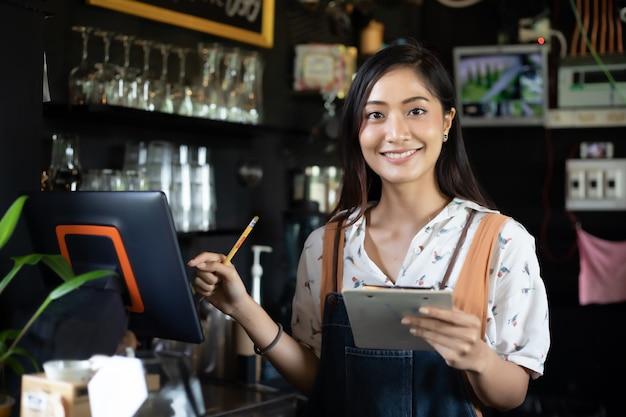 Aziatische vrouwen barista die en koffiemachine in de teller van de koffiewinkel glimlachen met behulp van