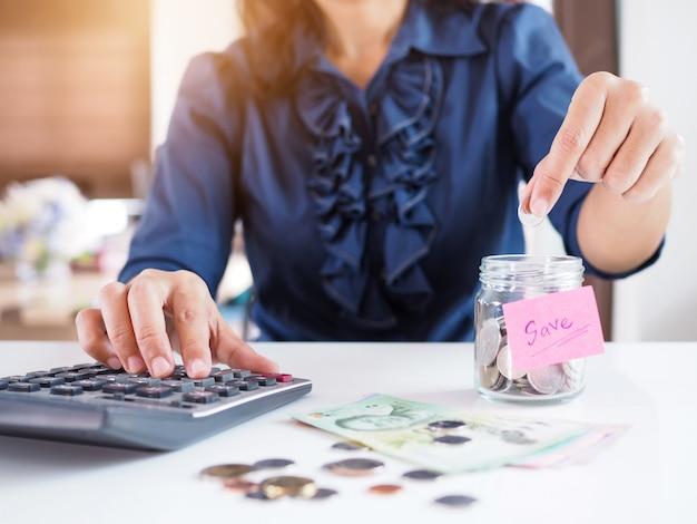 Aziatische vrouwen besparen geld met verzamelen munten in glazen flessen.