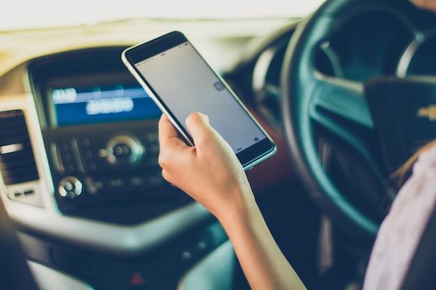 Aziatische vrouwen besturen auto's en gebruiken een smartphone op de weg.