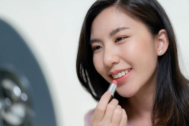 Aziatische vrouwen brengen lippenstift op hun lippen aan.