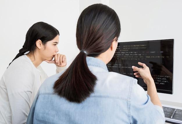 Aziatische vrouwen die aan een programmeercode werken