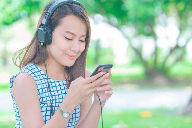 Aziatische vrouwen die aan muziek met hoofdtelefoons in de tuin luisteren.