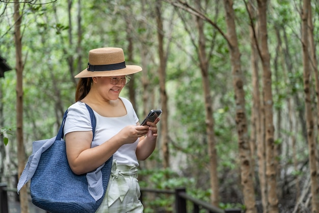 Aziatische vrouwen die aardbos reizen en smartphone gebruiken. wandelpad in de tropische jungle.