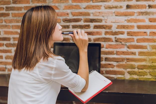 Aziatische vrouwen die bij de koffie met laptop denken die bedrijfsprojectactie woking