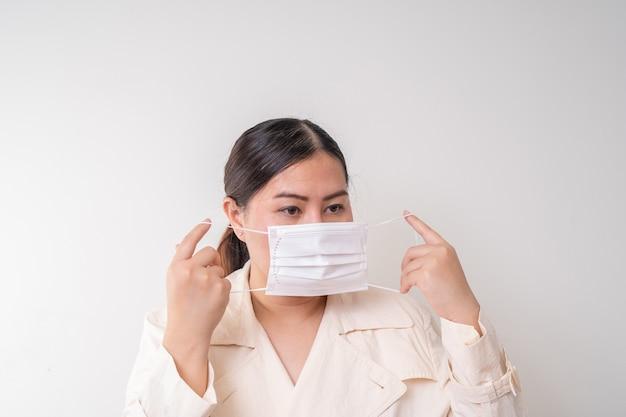 Aziatische vrouwen die chirurgisch gezichtsmasker dragen om griepziekte corona-virus te voorkomen