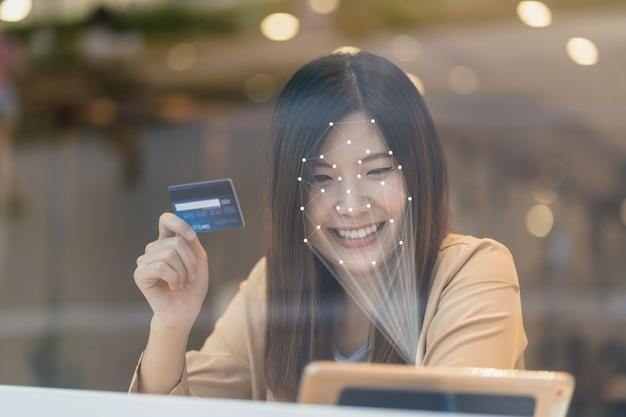 Aziatische vrouwen die de technologietablet gebruiken voor toegangscontrole door gezichtsherkenning