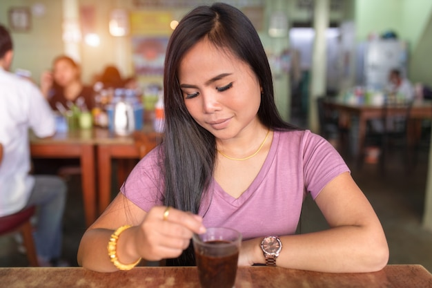 Aziatische vrouwen die de zitting van het koffieglas in de koffiewinkel drinken.