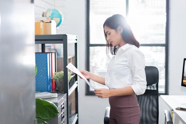 Aziatische vrouwen die documenten op het kantoor bekijken
