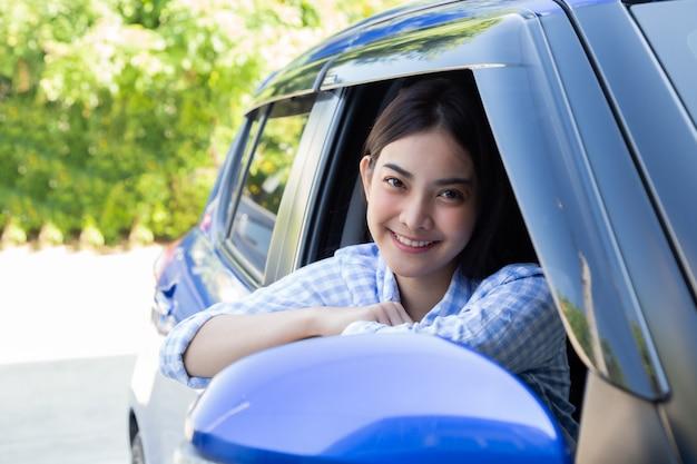 Aziatische vrouwen die een auto drijven en gelukkig glimlachen