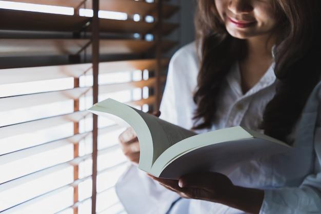 Aziatische vrouwen die een wit overhemd dragen, lezen een wit boek bij het raam in de slaapkamer