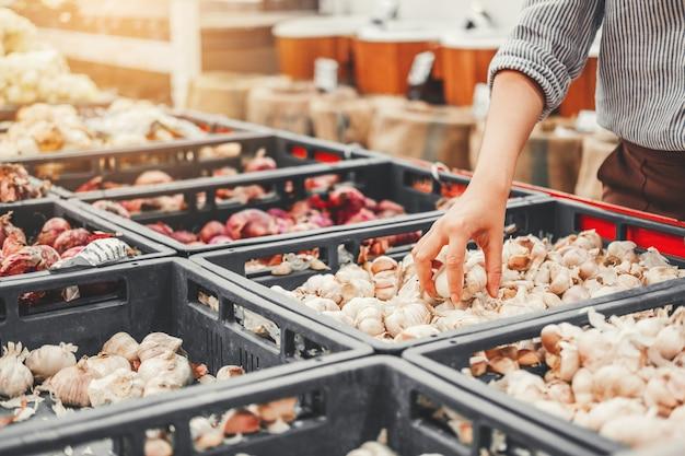 Aziatische vrouwen die gezonde voedselgroenten en vruchten in supermarkt winkelen