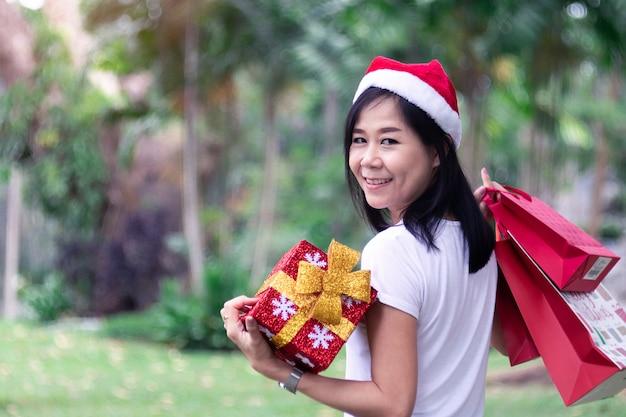 Aziatische vrouwen die gift en de zakken houden die met slijtageoorring winkelen