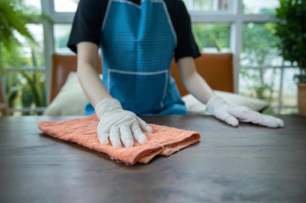 Aziatische vrouwen die handschoen en schoonmakende lijst thuis dragen