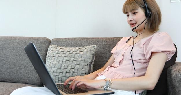 Aziatische vrouwen die hoofdtelefoon dragen en laptop videogesprekvergadering thuis gebruiken