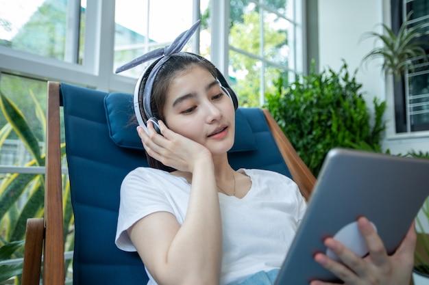 Aziatische vrouwen die hoofdtelefoons dragen en digitale tablet gebruiken op een ontspannende dag thuis