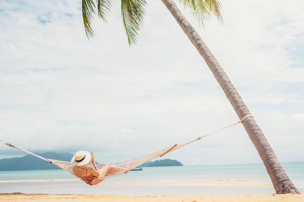 Aziatische vrouwen die in de vakantie van de hangmatzomer ontspannen op strand