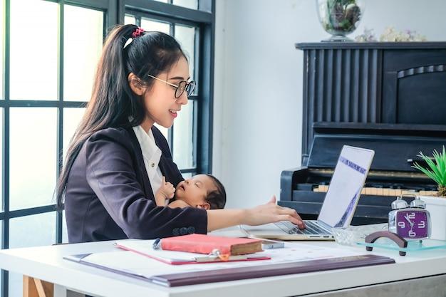Aziatische vrouwen die in zaken werken en kinderen thuis opheffen