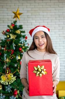 Aziatische vrouwen die kerstmanhoed met giftdoos dragen kerstmis, kerstmis, nieuw jaar, de winter, gelukconcept.