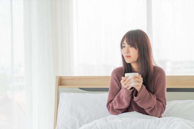 Aziatische vrouwen die koffie op bed in de ochtend drinken