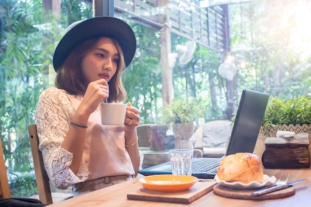 Aziatische vrouwen die koffiekop houden die laptop in koffie kijken
