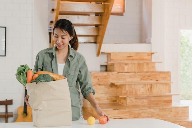 Aziatische vrouwen die kruidenierswinkel het winkelen document zakken thuis houden