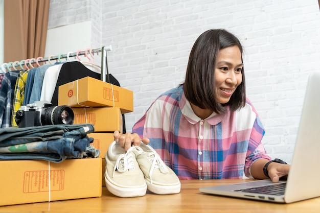 Aziatische vrouwen die laptop computer verkopende schoenen online werken