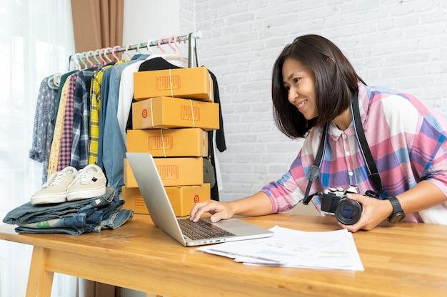 Aziatische vrouwen die laptop computer werken die online verkoopt