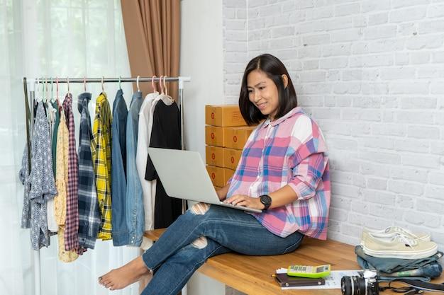 Aziatische vrouwen die laptop computer werken die thuis online verkopen