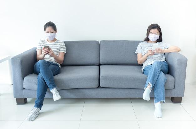 Aziatische vrouwen die maskers dragen die thuis werken die smartphone gebruiken om verspreiding van coronavirusbesmetting tijdens crisis van covid-19 te verminderen. werken vanuit huis en sociaal afstandsconcept.