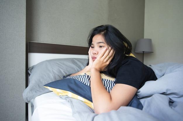Aziatische vrouwen die op het grijze bed liggen, ze ziet er verveeld en lui uit