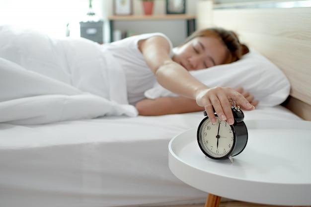Aziatische vrouwen die op wekker drukken terwijl zij in de ochtend op bed slaapt.